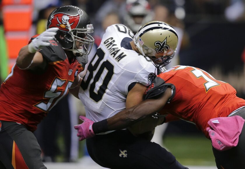 New Orleans Saints tight end Jimmy Graham (80) is hit by Tampa Bay Buccaneers cornerback Major Wright, right, and middle linebacker Dane Fletcher, in the first half of an NFL football game in New Orleans, Sunday, Oct. 5, 2014. (AP Photo/Bill Haber)