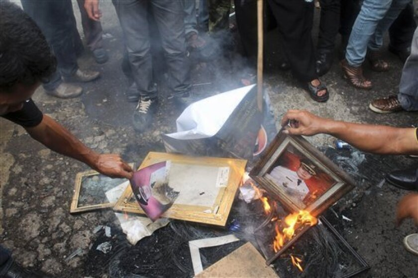 Protesters burn portraits of Garut District Chief Aceng Fikri during a protest in the town of Garut, West Java, Indonesia, Tuesday, Dec. 4, 2012. Hundreds of Indonesians rallied Tuesday to demand a Fikri's resignation following his text message divorce to a 17-year-old girl four days after their marriage alleging that she was not a virgin when they married as he had expected. Fikri says he spent about $26,000 on the wedding. (AP Photo)