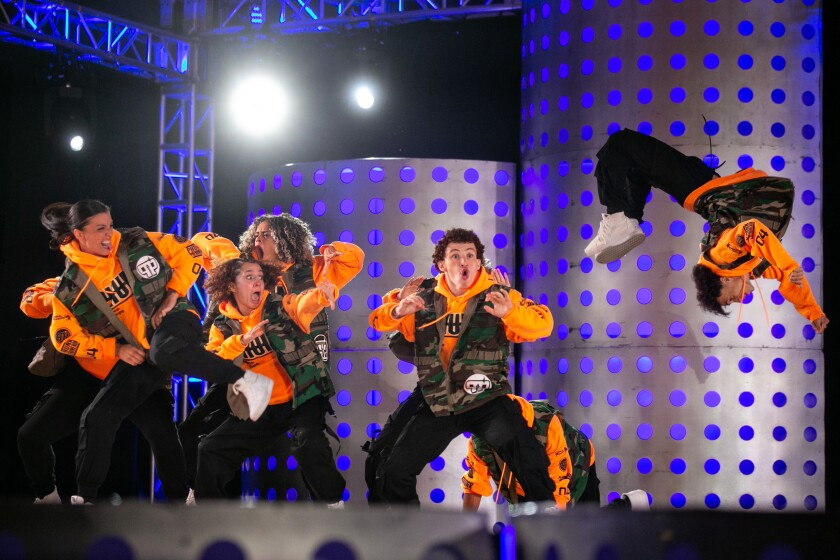 The dance crew Haus of Snap watches as a member does a flip.