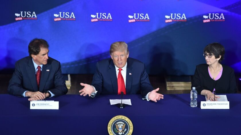 President Trump, center, flanked by Ohio Senate candidate, GOP Rep. Jim Renacci, left, and Ohio resident Sharlene Thornton, speaks during an event Saturday at the Cleveland Public Auditorium.