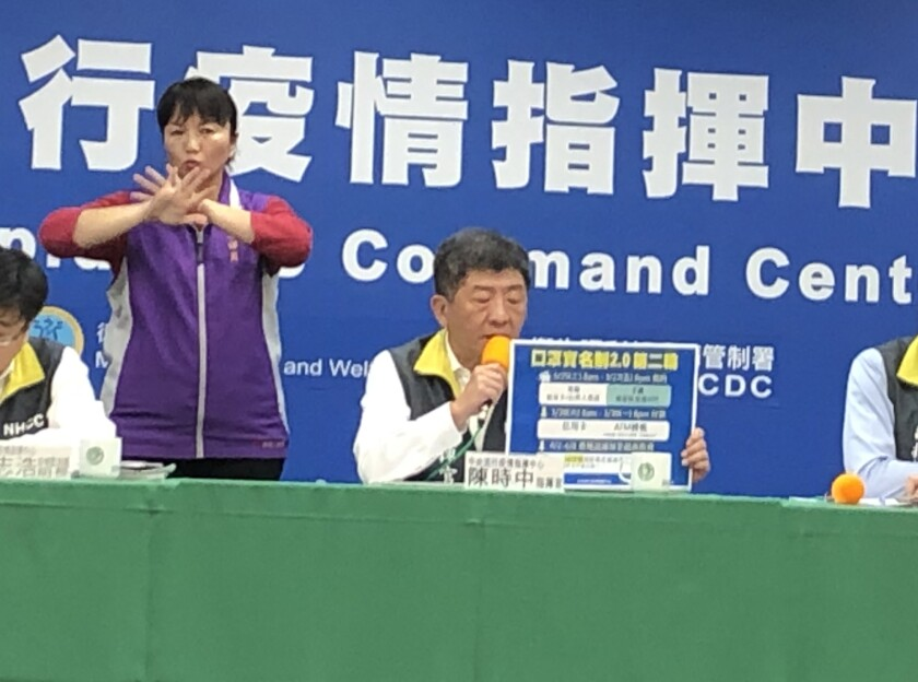 Taiwan's health and welfare minister, Chen Shih-chung, center, speaks at a Taipei news conference on March 30.