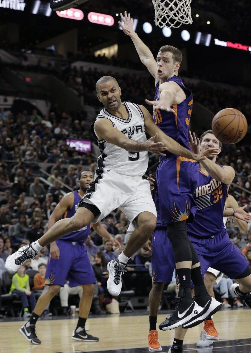 San Antonio Spurs' Tony Parker (9) is pressured by Phoenix Suns defenders Jon Leuer (30) and Mirza Teletovic (35) during the second half of an NBA basketball game, Monday, Nov. 23, 2015, in San Antonio. San Antonio won 98-84. (AP Photo/Eric Gay)