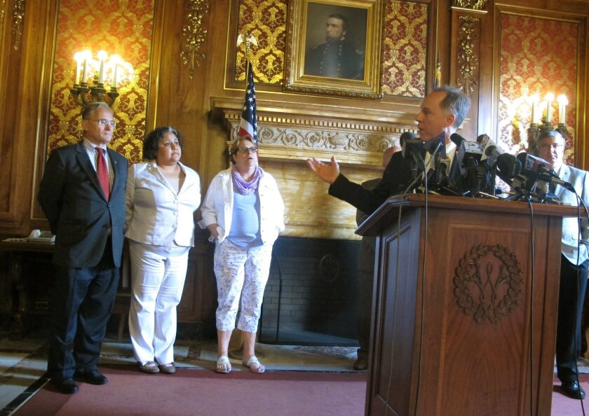 Republican Assembly Speaker Robin Vos, right, motions to Democratic Reps., from left: Peter Barca; JoCasta Zamarripa and Christine Sinicki at a news conference to announce a bill to pay for a new $500 million Milwaukee Bucks arena will pass on Tuesday, July 28, 2015, in Madison, Wis. (AP Photo/Scott Bauer)