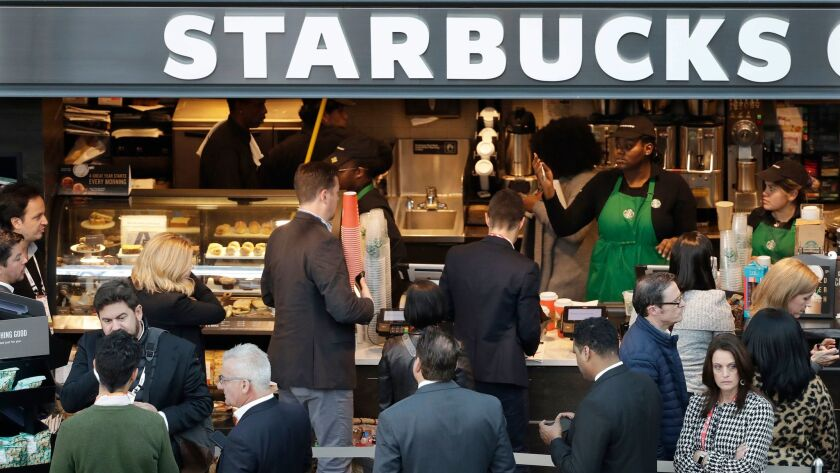 In this Sunday, Jan. 14, 2018, photo, people line up to order at a Starbucks in New York. Starbucks