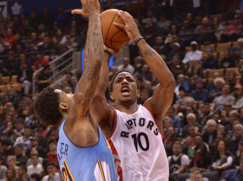 Raptors forward DeMar DeRozan, right, shoots over Denver Nuggets forward Wilson Chandler during the first half on Oct. 31.