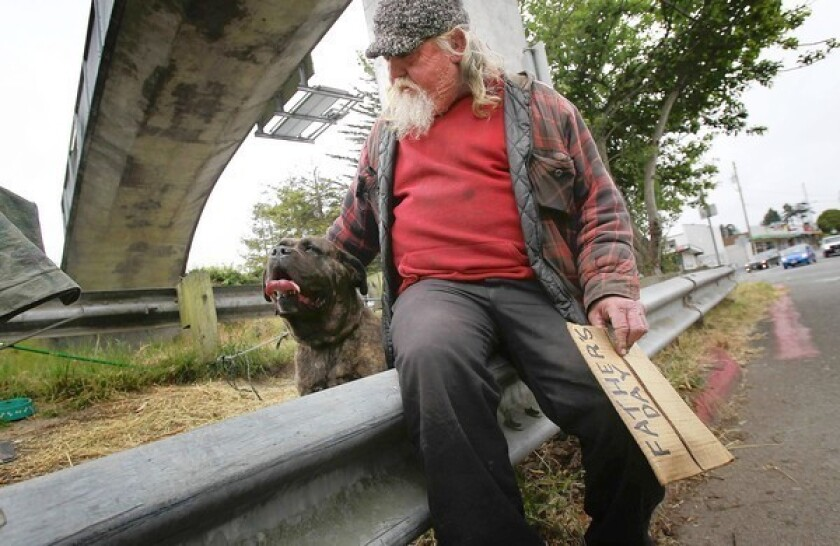 A homeless man who calls himself Big Al sits on a guardrail with his pet mastiff on California Highway 101 in Arcata last June. Big Al was prosecuted under the city's ordinance restricting panhandling.