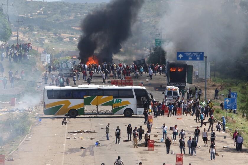 Maestros inconformes que bloqueaban una carretera federal se parapetan detrás de un autobús de pasajeros y otros camiones en llamas mientras se enfrentan con policías antimotines en el estado de Oaxaca, cerca del poblado de Nochixtlán, México, el domingo 19 de junio de 2016. (AP Foto/Luis Alberto Cruz Hernández)