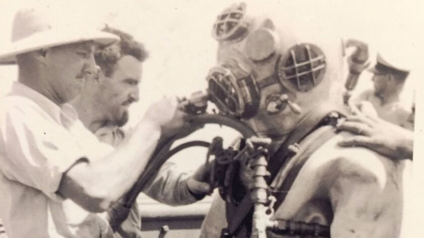 In this 1943 photo, Navy salvage diver Ken Hartle, second from left, helps adjust the helmet of a fellow diver during World War II. The Valley Center resident, who died Tuesday at the age of 103, was the Navy's oldest living Pearl Harbor salvage diver.