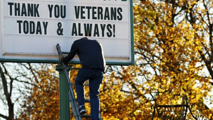 A man climbs down a ladder to get more letters to complete the message for veterans.