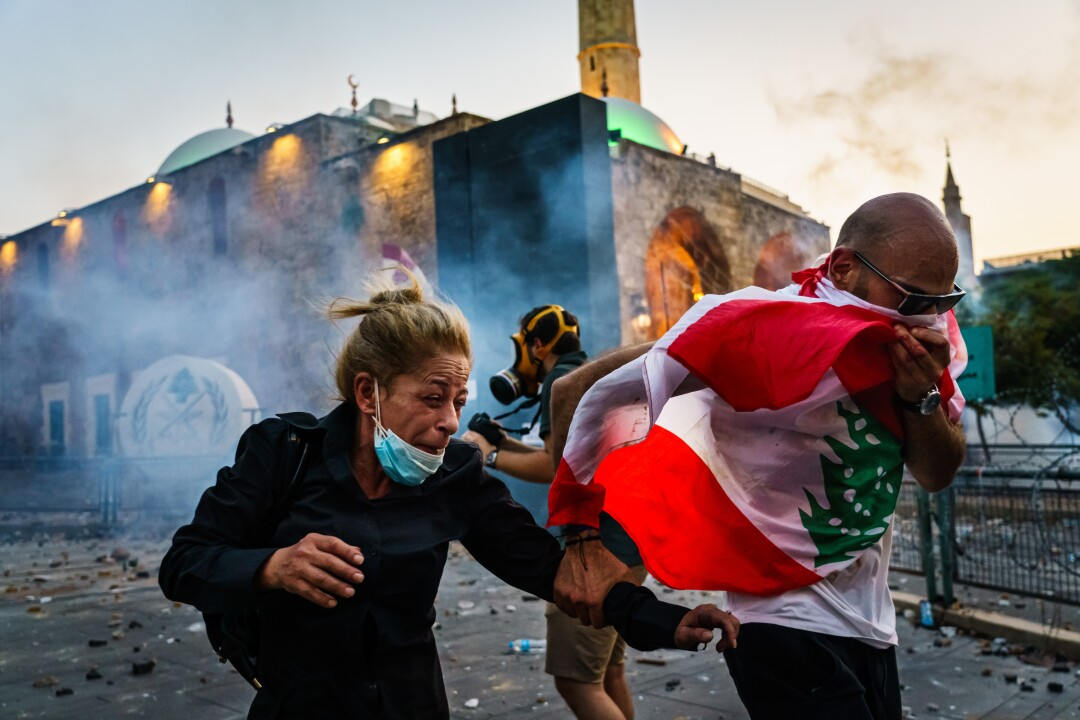 A woman grimaces and a man covers his nose and mouth with a flag as they run.