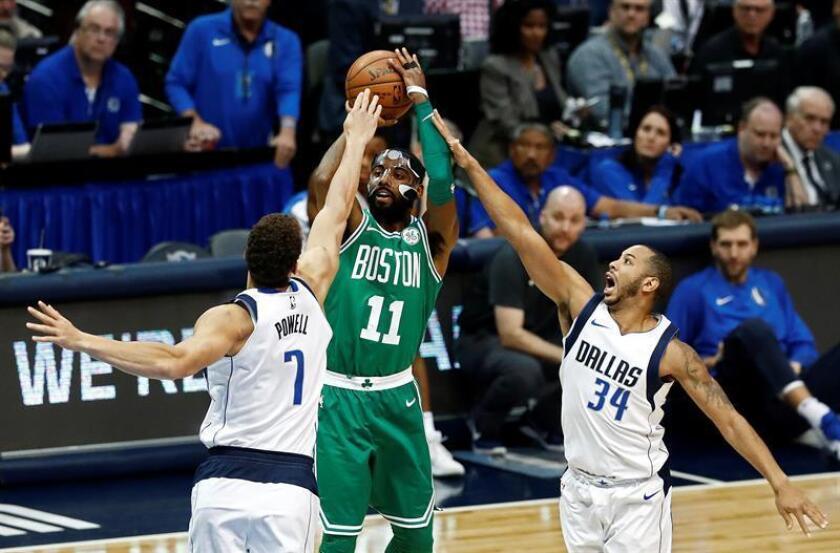 El jugador Kyrie Irving (c) de Boston Celtics lanza la pelota ante la marca de Devin Harris (d) y Dwight Powell (i) de Dallas, durante un juego entre Boston Celtics y Dallas Mavericks de la NBA, que se disputa en el American Airlines Center, en Dallas, Texas (Estados Unidos). EFE
