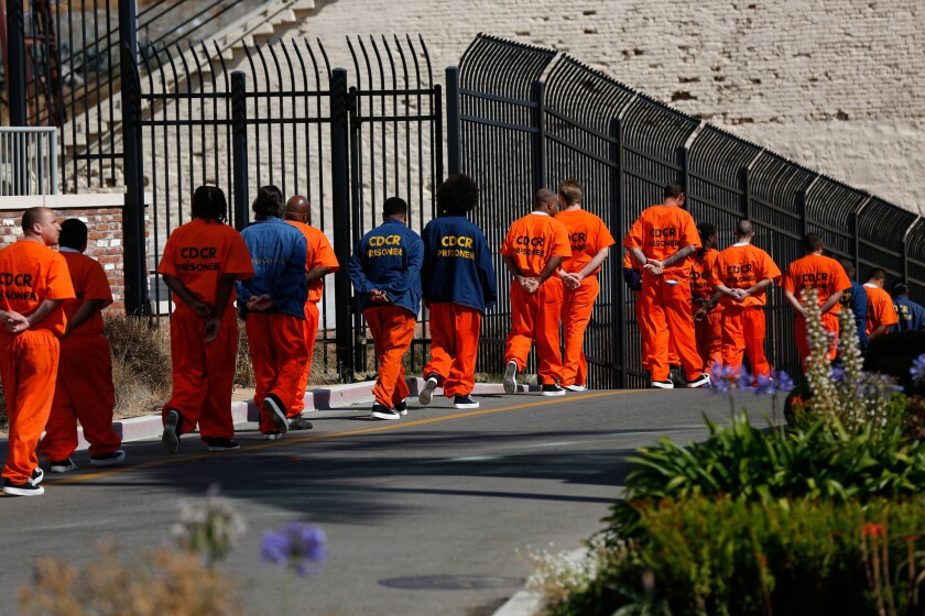 Inmates walk in file at San Quentin State Prison. A former inmate there was convicted this week of stealing the identities of his fellow prisoners to file fraudulent tax returns.