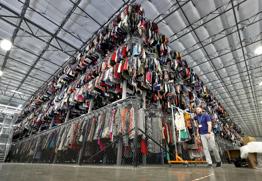 FILE - Thousands of garments are stored on a three-tiered conveyor system at the ThredUp sorting facility in Phoenix on March 12, 2019. A wardrobe purge is on for some as vaccinations have taken hold, restrictions have lifted and offices reopen or finalize plans to do so. The primary beneficiaries are secondhand clothing marketplaces, and brick-and-mortar donation spots. (AP Photo/Matt York, File)