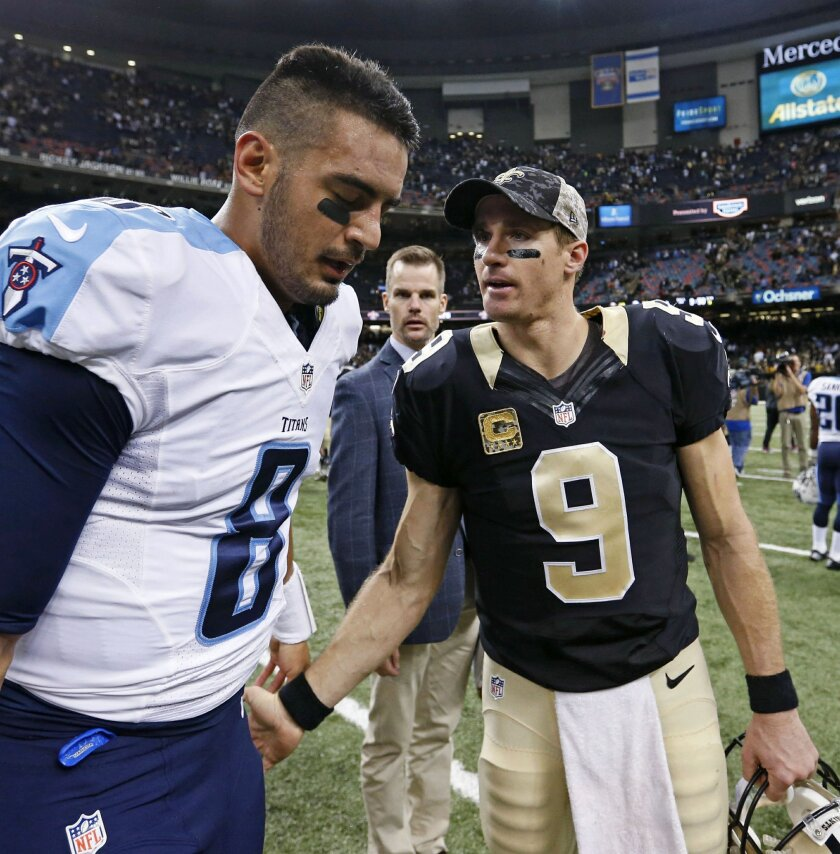 New Orleans Saints quarterback Drew Brees (9) greets Tennessee Titans quarterback Marcus Mariota (8) after their NFL football game in New Orleans, Sunday, Nov. 8, 2015. The Titans won 34-28. (AP Photo/Butch Dill)