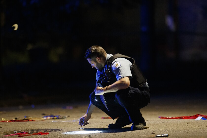 FILE - In this July 5, 2020, file photo, an officer investigates the scene of a shooting in Chicago. Still reeling from the coronavirus pandemic and street protests over the police killing of Floyd, exhausted cities around the nation are facing yet another challenge: A surge in recent shootings has left dozens dead, including young children. (Armando L. Sanchez/Chicago Tribune via AP, File)
