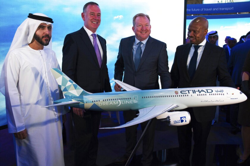 Etihad CEO Tony Douglas, second from left, helps present a model of the Boeing 787 Dreamliner at the Dubai Airshow in Dubai, United Arab Emirates, on Monday. Douglas is joined by Etihad COO Mohammad al-Bulooki, far left, and Boeing executives.