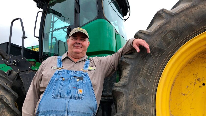 Bernard Peterson leans on a tractor at his farm in Loretto, Ky. At Peterson's farm, eight members of the family partnership collected a total of $863,560 in aid for crops they grow in seven counties.