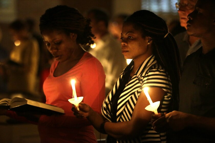 Princess Duo, left, and Mamie Mangoe, right, both natively of Liberia who now live in Dallas, stand holding lit candles as they pray during a service at Wilshire Baptist Church that was dedicated to Thomas Eric Duncan, Wednesday, Oct. 8, 2014, in Dallas. Nearly 150 persons attended the service for Duncan who died Wednesday of complication from Ebola. (AP Photo/Tony Gutierrez)