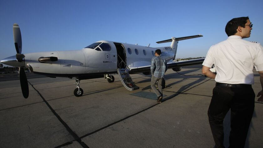 Capt. Chris Pimentel, right, waits for passengers to board a Surf Air commuter plane at Hawthorne Municipal Airport in 2015. Surf Air, an all-you-can-fly membership airline, is in a feud with the company that operated its planes in California since 2017.