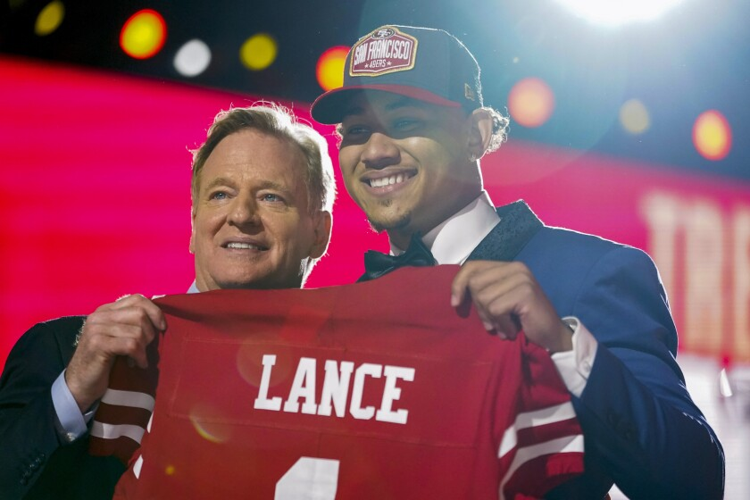 North Dakota State quarterback Trey Lance, right, holds a jersey with NFL Commissioner Roger Goodell after being chosen by the San Francisco 49ers with the third pick in the first round of the NFL football draft Thursday April 29, 2021, in Cleveland. (AP Photo/Tony Dejak)