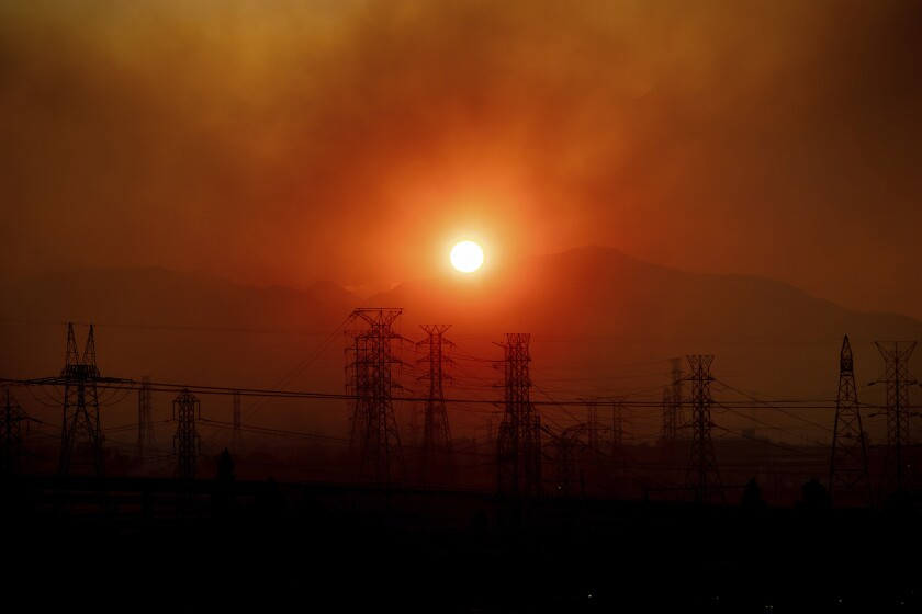 Smoke from the Saddleridge Fire hangs above power lines as the sun rises in Newhall, Calif., on Friday, Oct. 11, 2019. An aggressive wildfire in Southern California seared its way through dry vegetation Friday and spread quickly, destroying more than a dozen homes as tens of thousands of residents were ordered to get out of its way, authorities said. (AP Photo/Noah Berger)