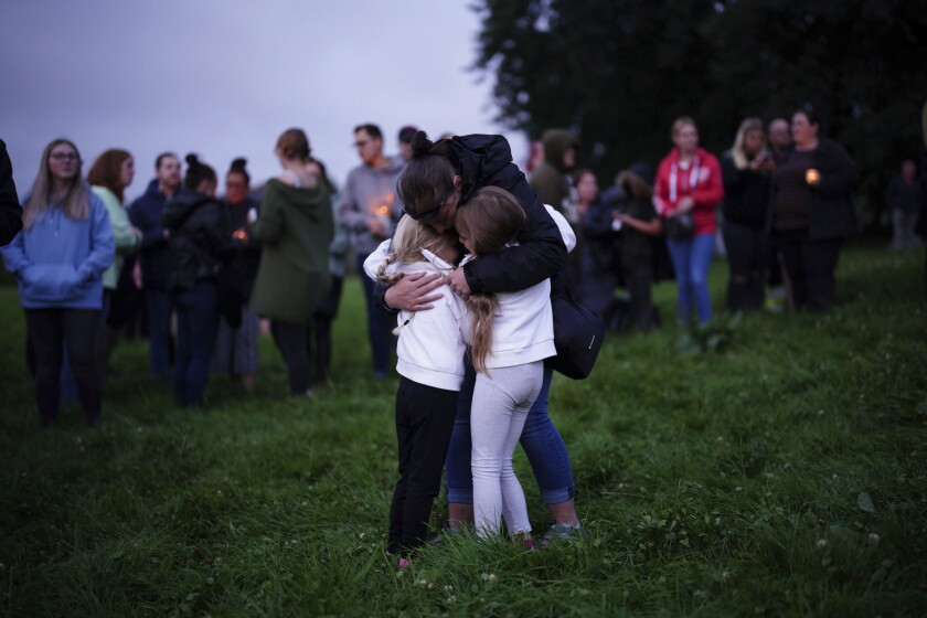A woman consoles children during an outdoor vigil for the victims of a mass shooting