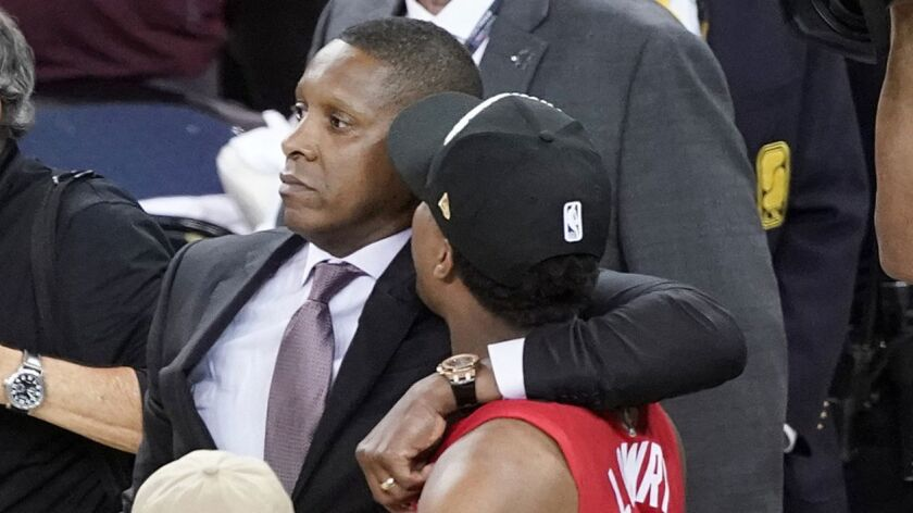 Toronto Raptors president Masai Ujiri walks with guard Kyle Lowry onto the court to celebrate their NBA title.