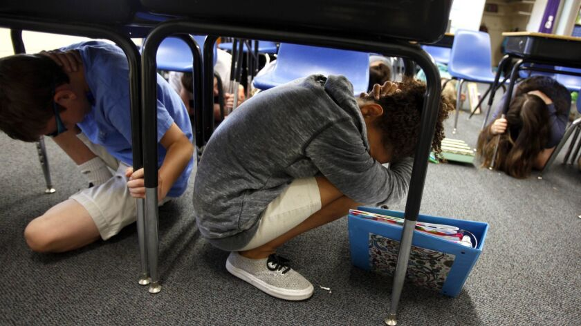 Sixth-graders take cover under their desks at the beginning of an earthquake drill at Pasadena Christian School in 2014.