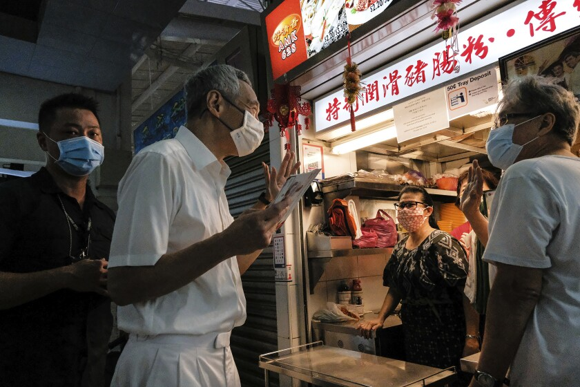 Singapore Prime Minister and Secretary-General of the People's Action Party Lee Hsien Loong, second left, wears a face mask while talking to food vendors at a local market at Yio Chu Kang while on the campaign trail in Singapore July 3, 2020. Singaporeans go to the polls on July 10 in Southeast Asia's first election since the coronavirus pandemic began, with the health crisis and an economic recession expected to bolster Prime Minister Lee's party and extend its unbroken rule. (AP Photo/Ee Ming Toh)