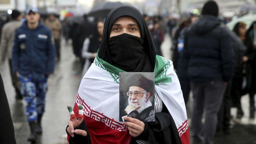 An Iranian woman holds up a portrait of Iranian Supreme Leader Ayatollah Ali Khamenei, as she makes
