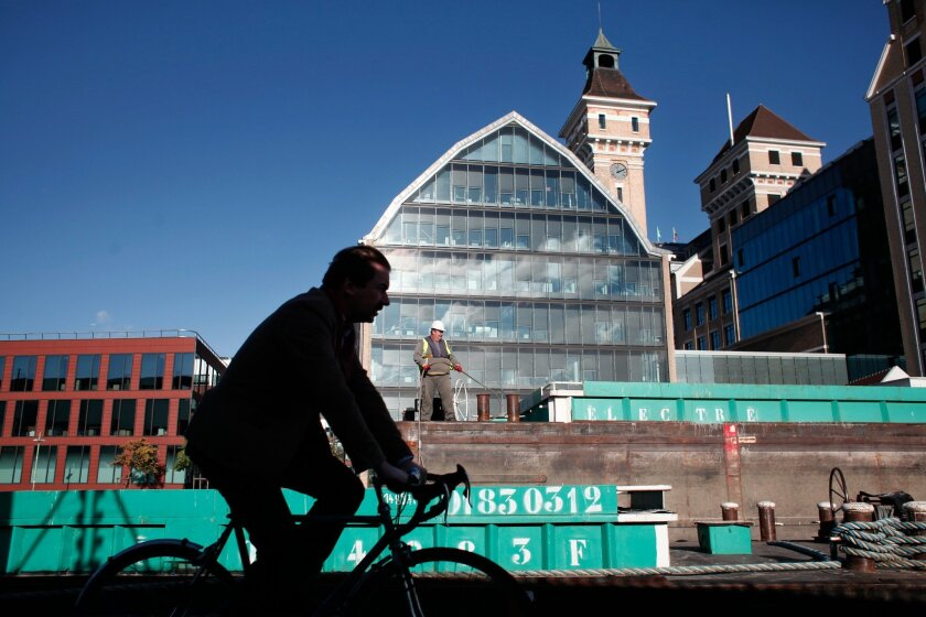 A man rides on a bicycle along the Ourcq canal, in Pantin, east of Paris, Wednesday, Nov. 12, 2014.  Pantin, a once-gritty Paris suburb, is sometimes compared to Brooklyn, New York. Both areas have gentrified, with artists and galleries moving in to old warehouses and real estate prices shooting up