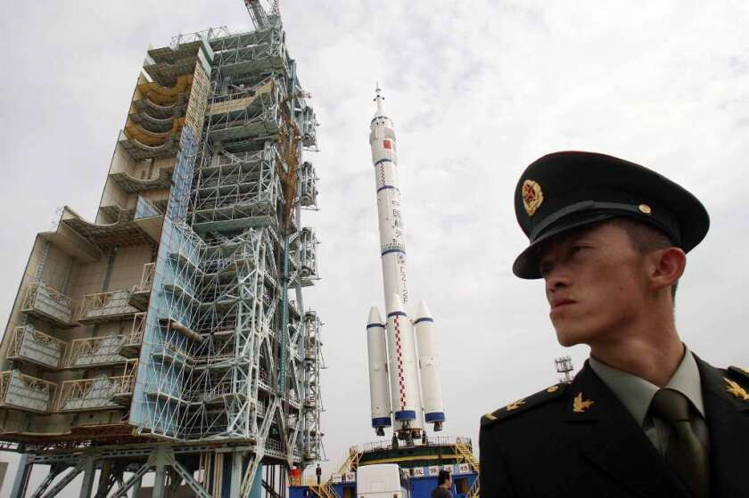 A Chinese soldier stands guard near the Shenzhou 7 manned spaceship in 2008. Last week, China successfully launched a lunar probe into space to land a rover on the moon.