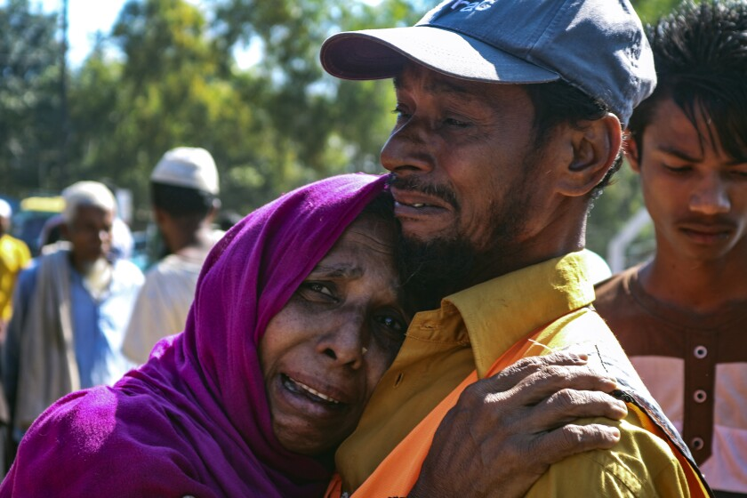 A Rohingya refugee woman who is among those being moved to an island called 'Bhasan Char' cries outside a transit area where they are temporally housed in Ukhiya, Bangladesh, Thursday, Dec.3, 2020. (AP Photo/ Shafiqur Rahman)