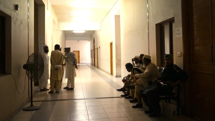Tribesmen talk as they wait to enter the FATA Tribunal for a hearing.
