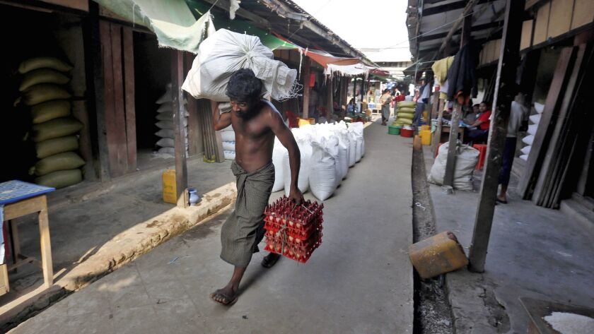 A Muslim man carries goods inside the market in ButheeTaung town, Rakhine state, in western Myanmar.