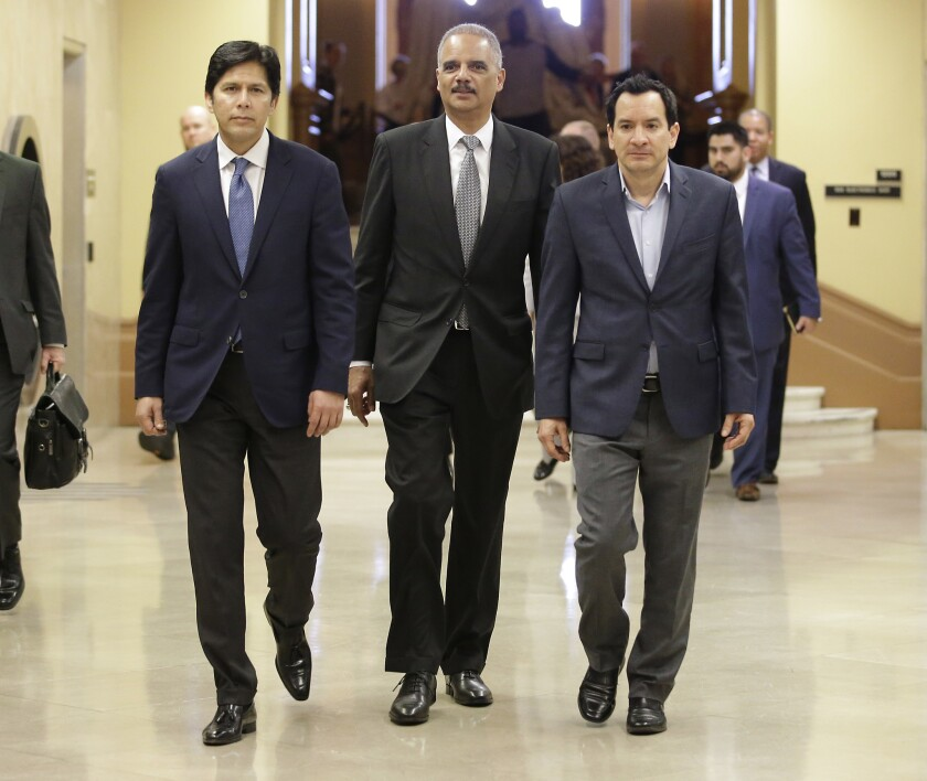 Former U.S. Atty. Gen. Eric Holder, center, flanked by California Senate President Pro Tem Kevin de León (D-Los Angeles), left, and Assembly Speaker Anthony Rendon (D-Paramount) walks to a meeting with Gov. Jerry Brown on Feb. 7 in Sacramento.