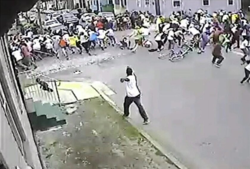 Surveillance footage released by the New Orleans Police Department shows a man apparently firing a gun into a crowd during a Mother's Day parade Sunday.