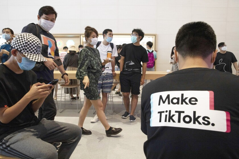 In this July 17, 2020, file photo, a visitor to an Apple store wears a t-shirt promoting Tik Tok in Beijing. TikTok executives told a Senate committee on Friday, Sept. 25, 2020, that they lobbied Australian lawmakers but did not engage with investigators before the government concluded that the video-sharing app did not pose a security threat. (AP Photo/Ng Han Guan, File)