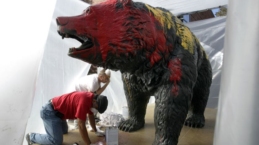 Workers clean off red and yellow paint from the Bruin Bear in 2009. In November, vandals again defaced the statue.