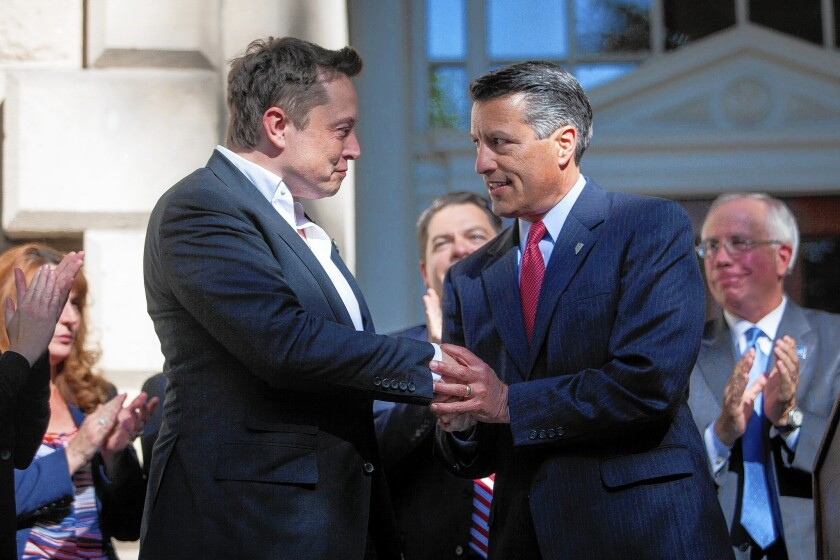 Elon Musk, left, CEO of Tesla Motors, at a Capitol news conference with Nevada Gov. Brian Sandoval.