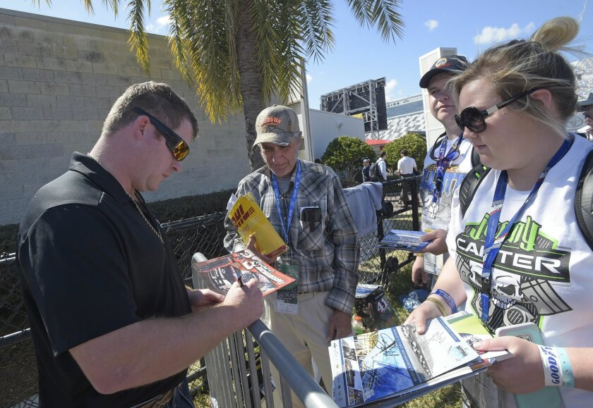Robert Richardson Jr, left, signs autographs for fans after practice for Sunday's NASCAR Daytona 500 Sprint Cup series auto race at Daytona International Speedway in Daytona Beach, Fla., Friday, Feb. 19, 2016. The farmer who hasn't made a NASCAR start since 2009 was the biggest surprise to crash th