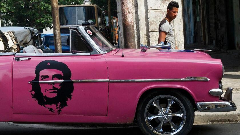 Foto de archivo en Cuba. Un vehículo estadounidense de modelo viejo se pasea por la Habana con la imagen del líder revolucionario Ernesto Che Gyevara.
