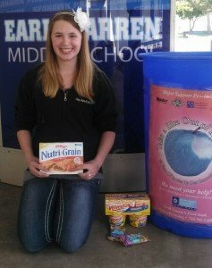 Chloe Williams at Earl Warren Middle School with the food donation bin, kicking off the Hands Against Hunger food drive.