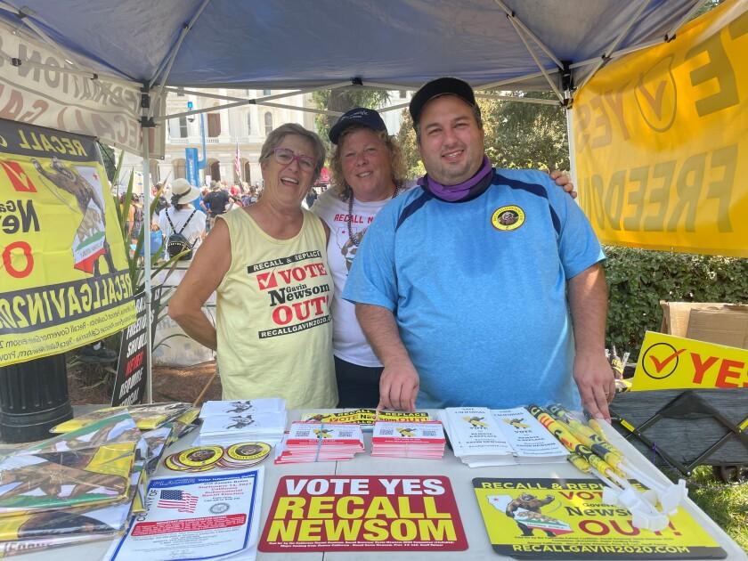 Stephanie Suela, Linda Rich and Matt Francis man a booth in support of recalling Gov. Gavin Newsom.