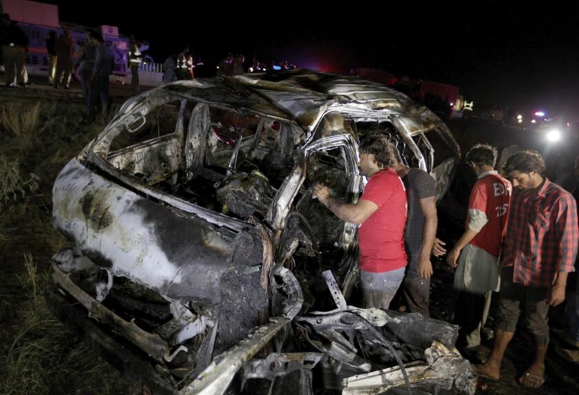 Socorristas examinan los restos calcinados de una furgoneta de pasajeros en el sitio de un accidente en una carretera a unos 50 kilómetros de Karachi, Pakistán, el sábado, 26 de septiembre del 2020. Trece personas murieron en el accidente. (AP Foto/Fareed Khan)