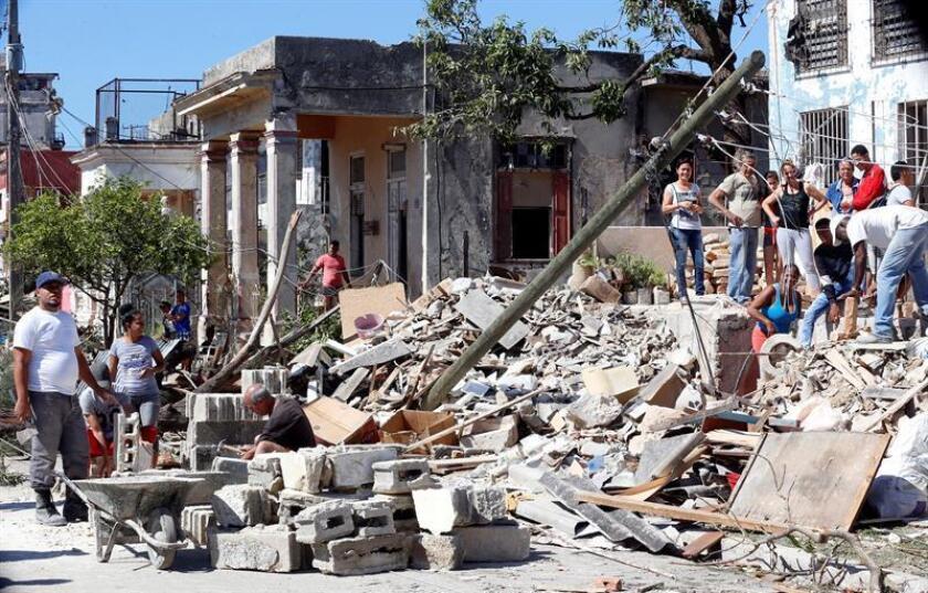 Varias personas realizan labores de recuperación y limpieza de aéreas con muchos escombros en La Habana (Cuba). EFE