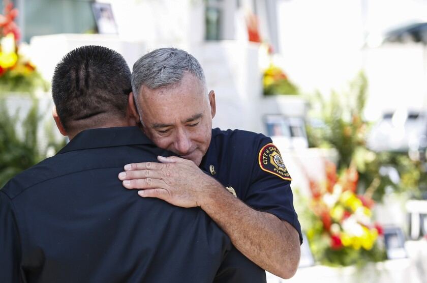 Guillermo Flores, left, whose brother David, 11, was killed in the attack, hugs battalion chief David Connor, who was there that day as a rookie firefighter. It was a first time meeting for both men, and the first time Connor had met a relative of one of