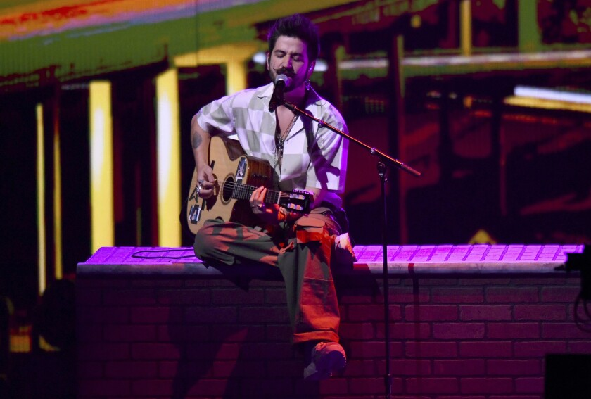"""FILE - Camilo performs for Premio Lo Nuestro on Feb. 14, 2021, in Miami. Camilo earned the most Latin Grammy nominations on Tuesday, Sept. 28, 2021, garnering ten, including ones for song of the year and record of the year, for """"Vida de Rico"""", and album of the year for """"Mis Manos"""" (My hands.) The 22nd Latin Grammy Awards will be held on Nov. 18. (AP Photo/Jim Rassol, File)"""
