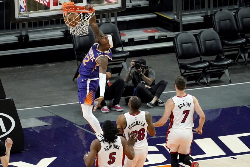 Torrey Craig, de los Suns de Phoenix, realiza una clavada en el partido disputado el martes 13 de abril de 2021 ante el Heat de Miami (AP foto/Matt York)