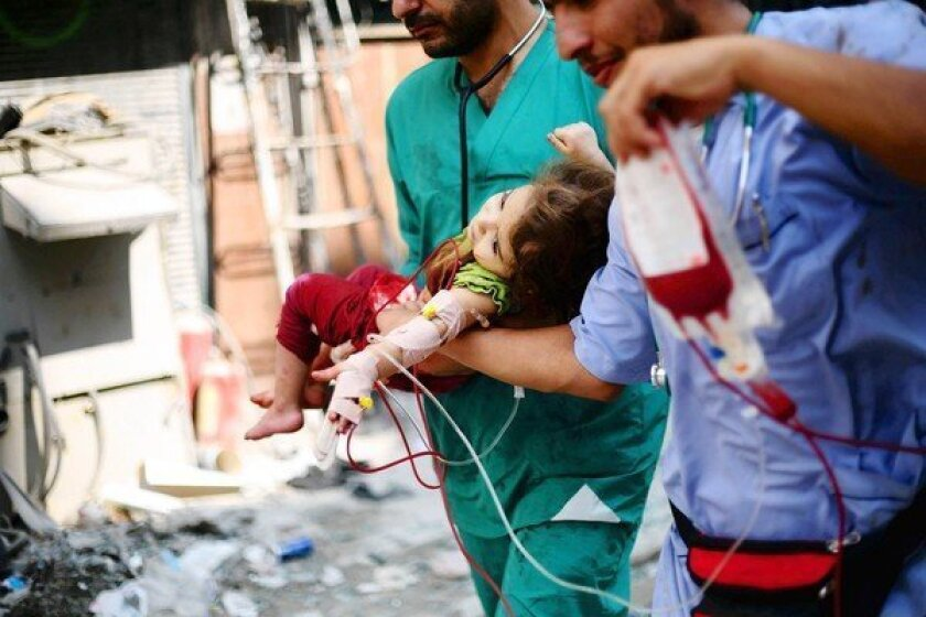 Medics carry a Syrian child injured Tuesday in government shelling of rebel-controlled areas of Aleppo. To the south, government forces killed about 60 people in airstrikes on Maarat Numan.